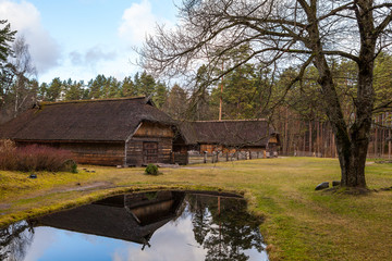View of the rustic farm building near small pond. Wooden architecture of North and Baltics