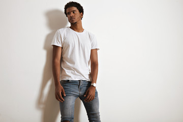 Thoughtful black young man in blank white t-shirt and jeans isolated on white background and looks aside