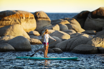 Young woman paddle boarding on a lake.
