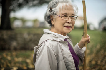 Portrait of a senior woman holding a walking stick.