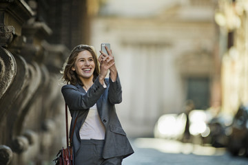 Smiling young businesswoman takes a photo with her cell phone as she walks home after work.