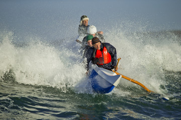 Group of middle-aged friends have fun out on their canoe in the ocean waves.