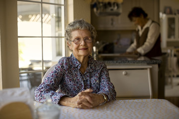 Portrait of a cheerful elderly woman sitting at her kitchen table while her daughter helps out with the dishes.