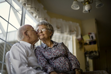 Affectionate elderly couple sit at the kitchen window together.