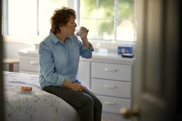 Mature woman drinks water to wash down her tablets.