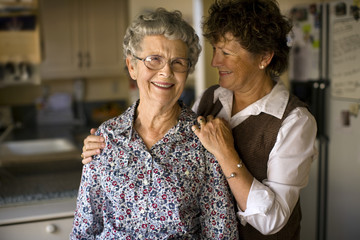 Smiling mature woman gives her elderly mother an affectionate squeeze.
