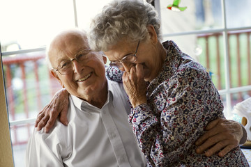 Affectionate elderly couple share a laugh as they sit at the kitchen window together.