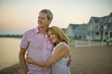 Mature couple smiling and embracing on the beach at sunset.