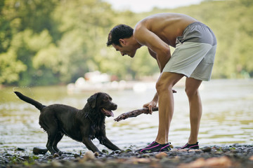 Man playing fetch with his pet dog outdoors