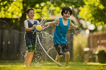 Two young boys playing with a sprinkler.