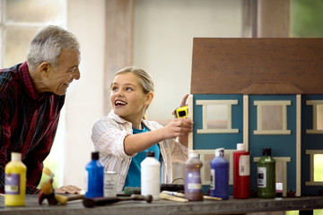 Smiling young girl measuring a doll house while her grandfather looks on.