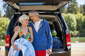 Happy senior couple looking at each other while standing next to their SUV while on holiday.