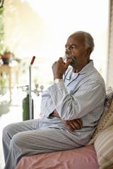 Unwell elderly man uses oxygen mask.