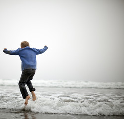 Small boy jumping in shallow water at beach.