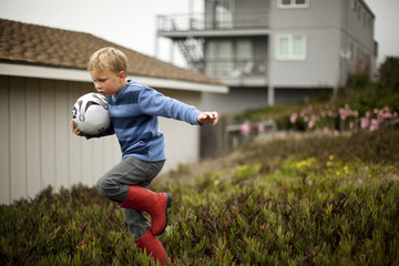 Young boy holding a soccer ball as he runs away.