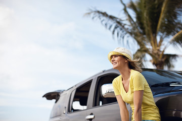 Smiling woman leaning on car outside.