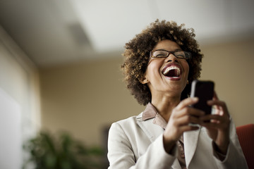 Businesswoman laughing as she looks at cell phone.