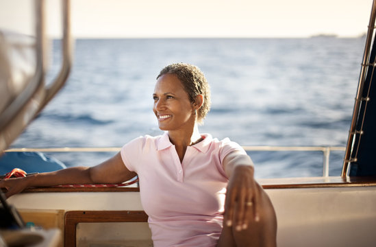 Mature woman leaning back relaxing on boat, looking at view.