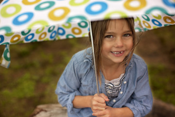 Close-up of young girl holding an umbrella.