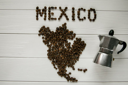 Map of the Mexico made of roasted coffee beans laying on white wooden textured background with coffee maker