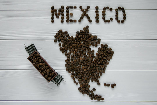 Map of the Mexico made of roasted coffee beans laying on white wooden textured background with toy train