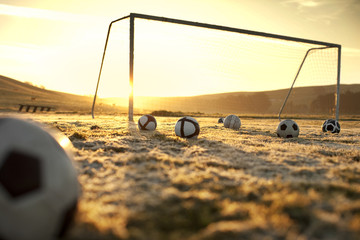 Soccer balls on an empty field at sunset.