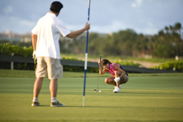 Woman at golf course sets up shot.