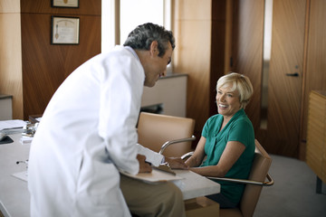 Mature doctor consulting with a patient in his office.