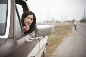 Young woman applying make-up while sitting in her car