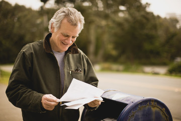 Man standing next to post box reading letter
