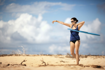 Young woman using a hula hoop at the beach.