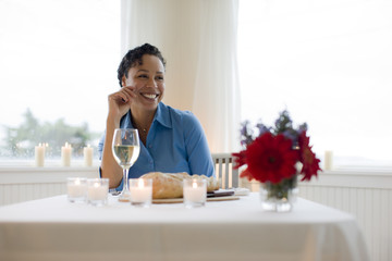 Woman sitting at table with meal and glass of wine