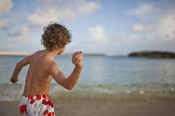 Young boy throwing a stone into the sea on a beach.