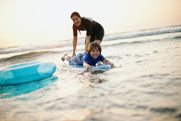 Mother teaching young son how to ride a wave on a surfboard.