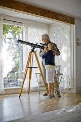 Senior man assisting his young granddaughter  with looking through a telescope.