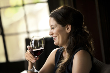 Laughing mid-adult woman holding a glass of red wine.
