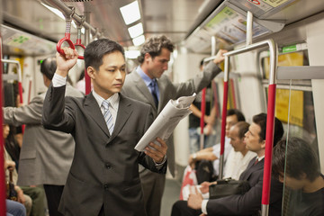 Businessman reading a newspaper while on a train.