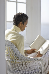 Mid-adult woman sitting in a wicker chair reading a book in a sunny room.