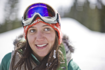 Smiling young woman wearing ski goggles  on her forehead.