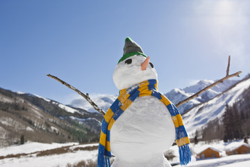 Snowman wearing s striped scarf an knitted hat in a wintry landscape.