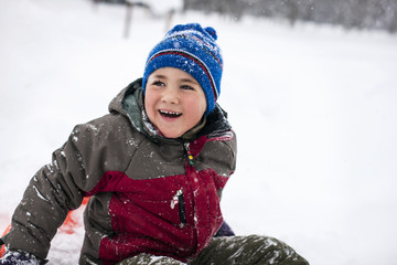 Laughing boy having fun wearing a padded jacket and knit hat while playing in the snow.