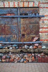 Old abandoned brick wall with rust iron gates. Urban and industrial background.