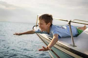 Young boy having fun at the front of a boat in the ocean.