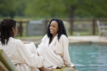 Young woman laughing while sitting next to a swimming  pool wearing a robe.