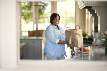 Portrait of a smiling woman holding a paper bag of groceries in a light and airy kitchen.