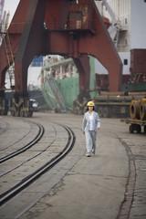 Mid-adult business woman walking along a shipping yard.
