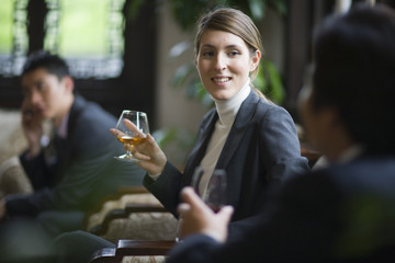 Young businesswoman holding a glass of alcohol while seated with colleagues in a restaurant.