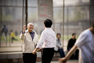 Two mature men playing basketball in a park.