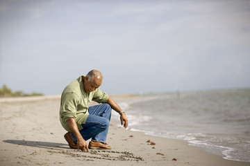 Mature adult man drawing in the sand on a beach.