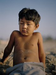 Portrait of a small boy resting on the beach.